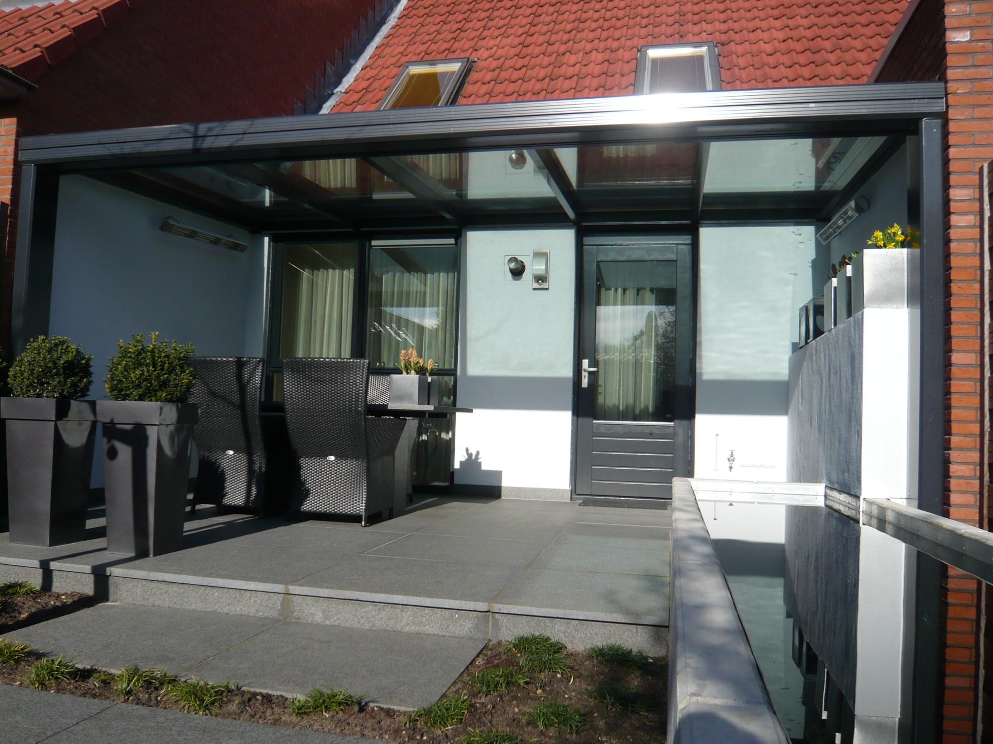 Grijze Aluminium terrasoverkapping met glas en plat dak tegen woning tussen 2 muren.