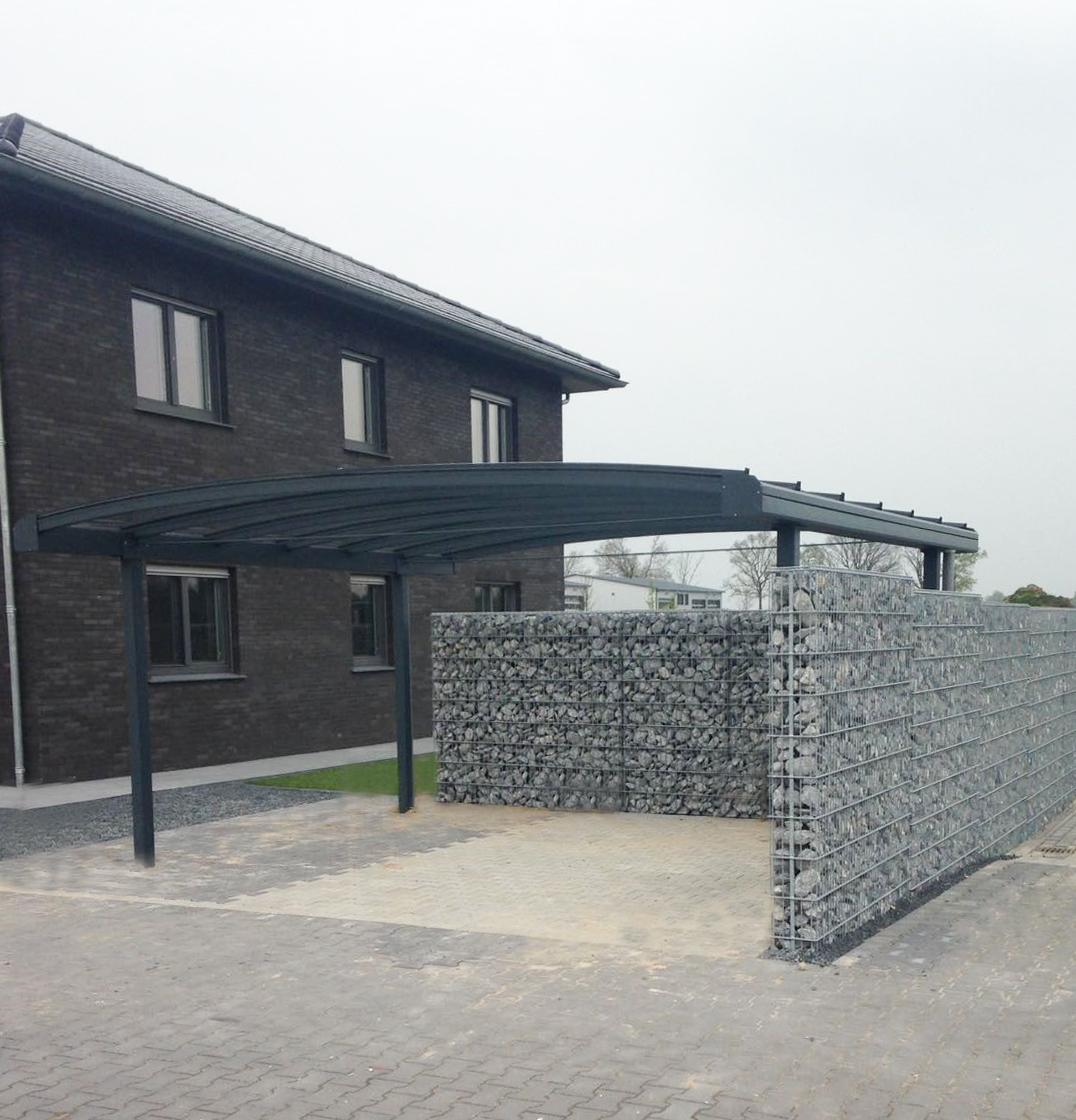 Brede gebogen aluminium carport met glas. Omheind met schanskorfmuur met grijze stenen naast woonhuis.