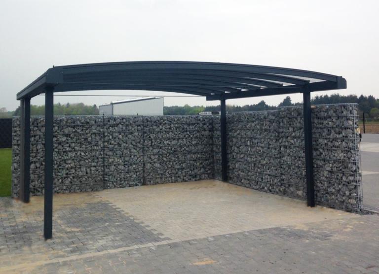 Gebogen aluminium carport met glas. Omheind met schanskorfmuur met grijze stenen.