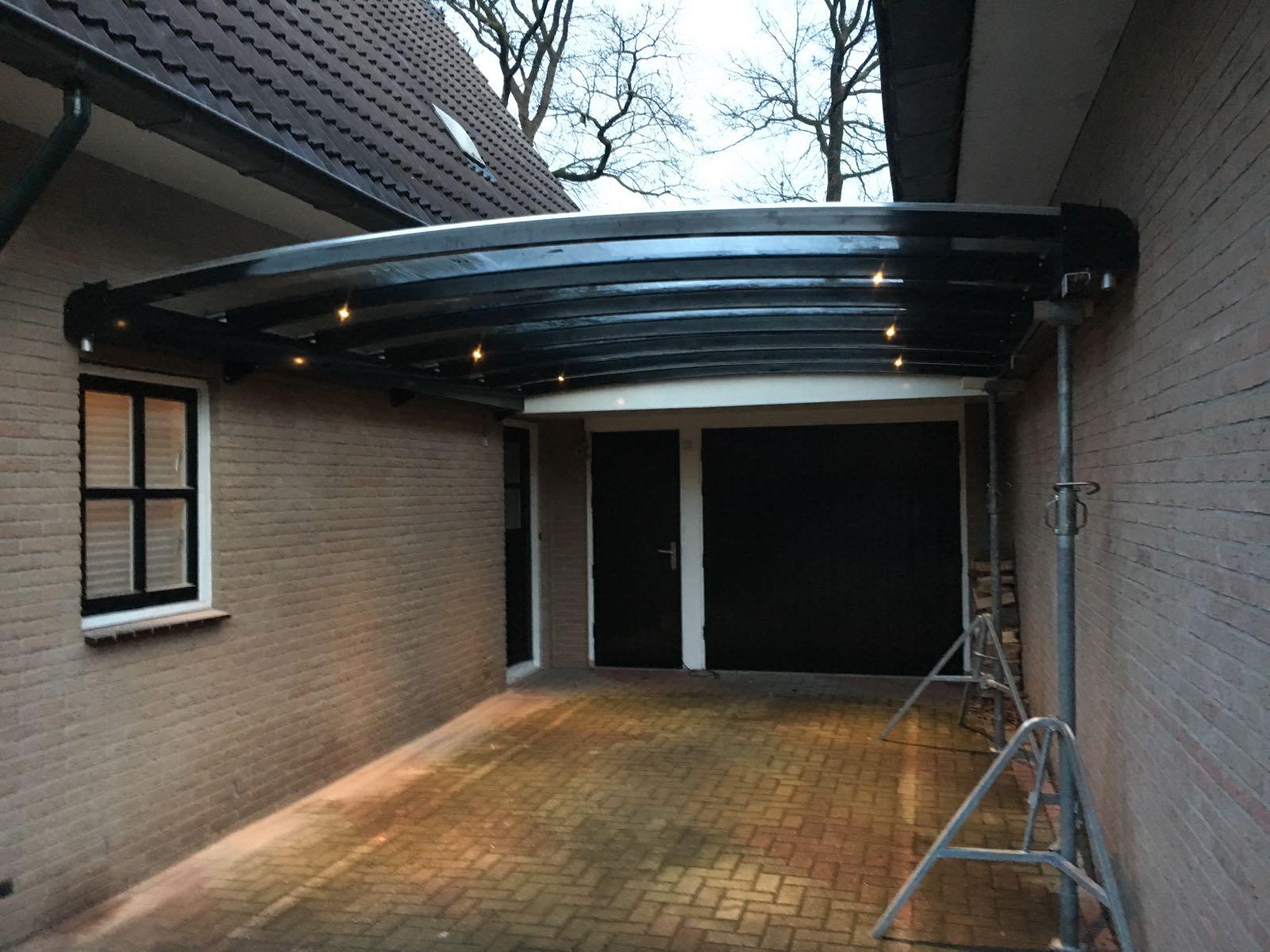 Luxe carport met verlichting en glas tussen twee huizen