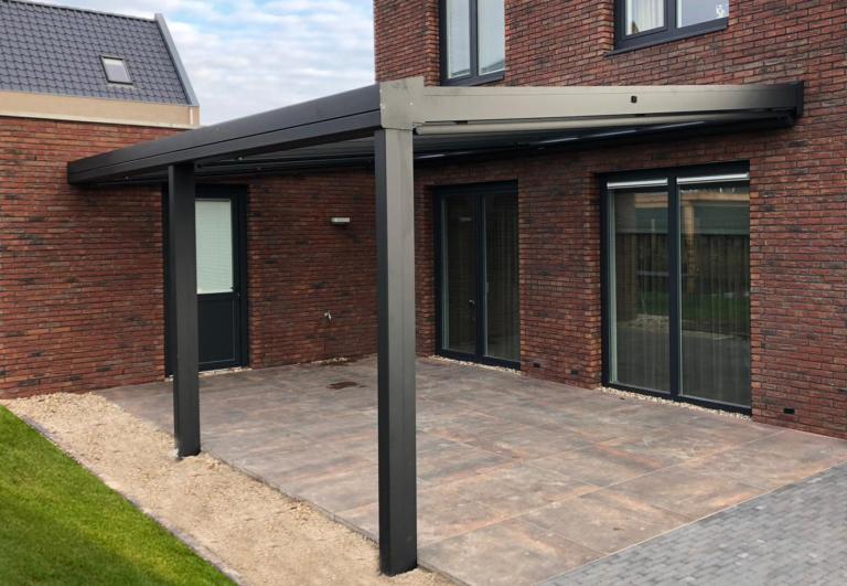 Zwarte terrasoverkapping met glazen lessenaars dak aan gevel van huis. Terrasoverkapping ook mogelijk als carport aan de woning