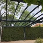 Onderaanzicht van dubbele gebogen aluminium carport met glas bevestigd aan witte stenen gebouw met groene deuren.