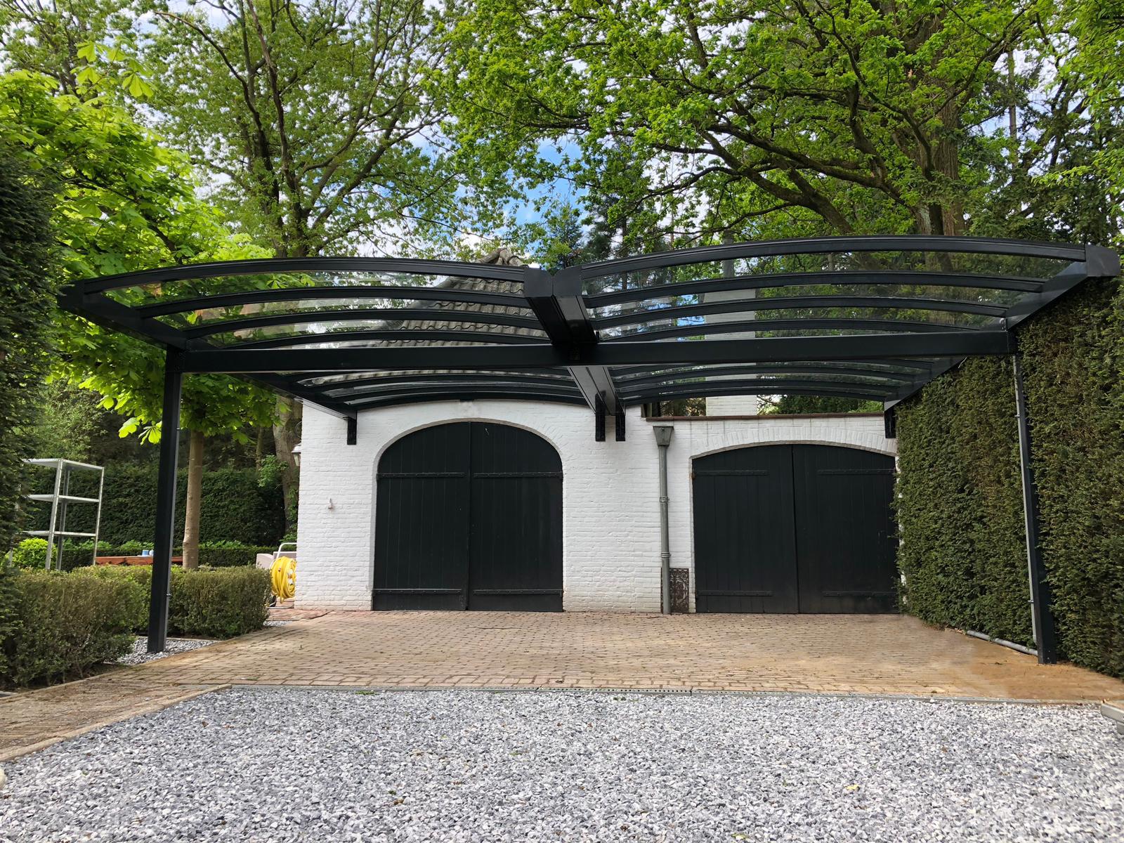 Vooraanzicht van dubbele gebogen aluminium carport met glas tegen witte stenen garage met groene deuren.