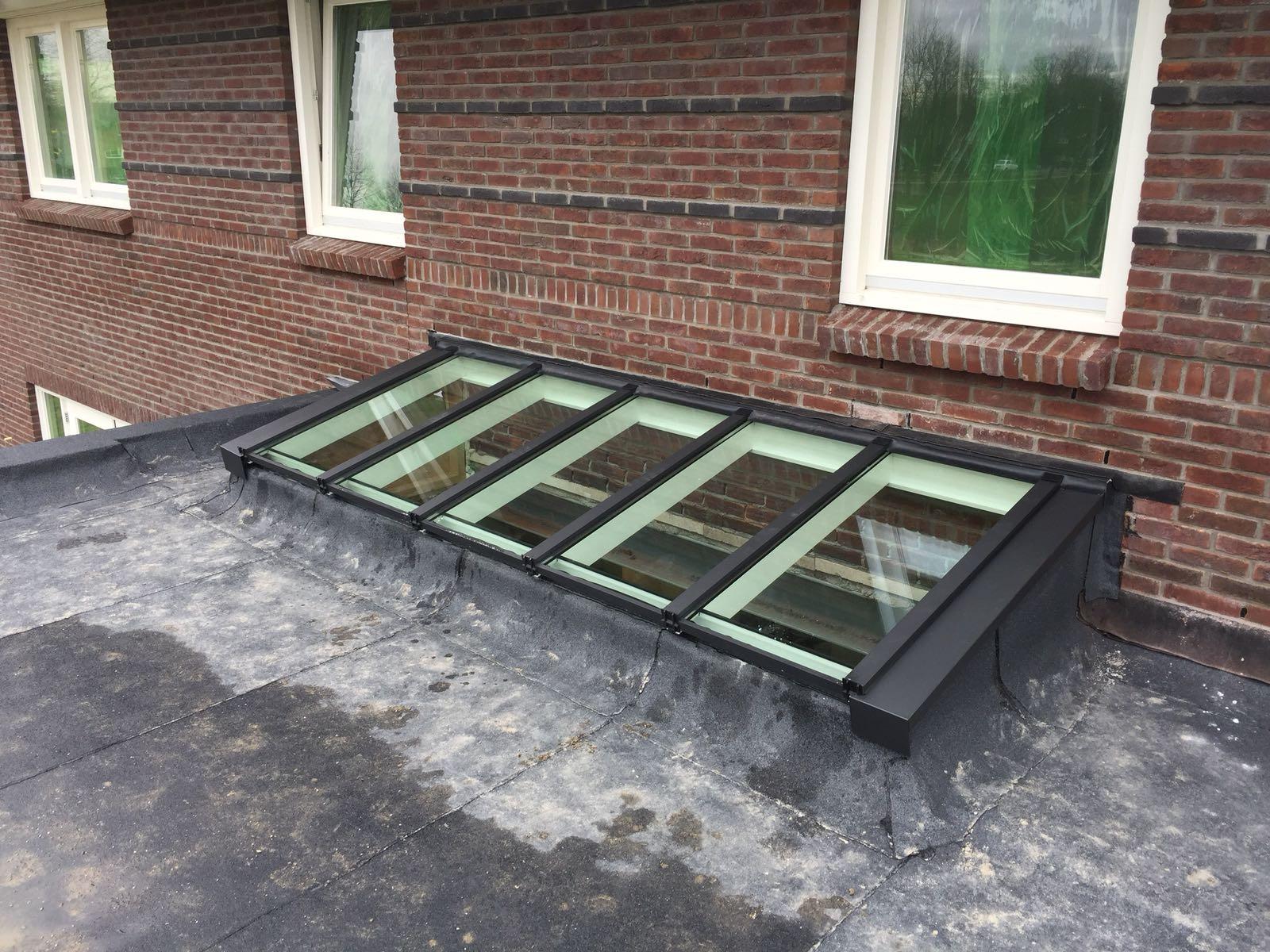Zwarte lichtstraat lessenaarsdak op plat dak tegen gevel