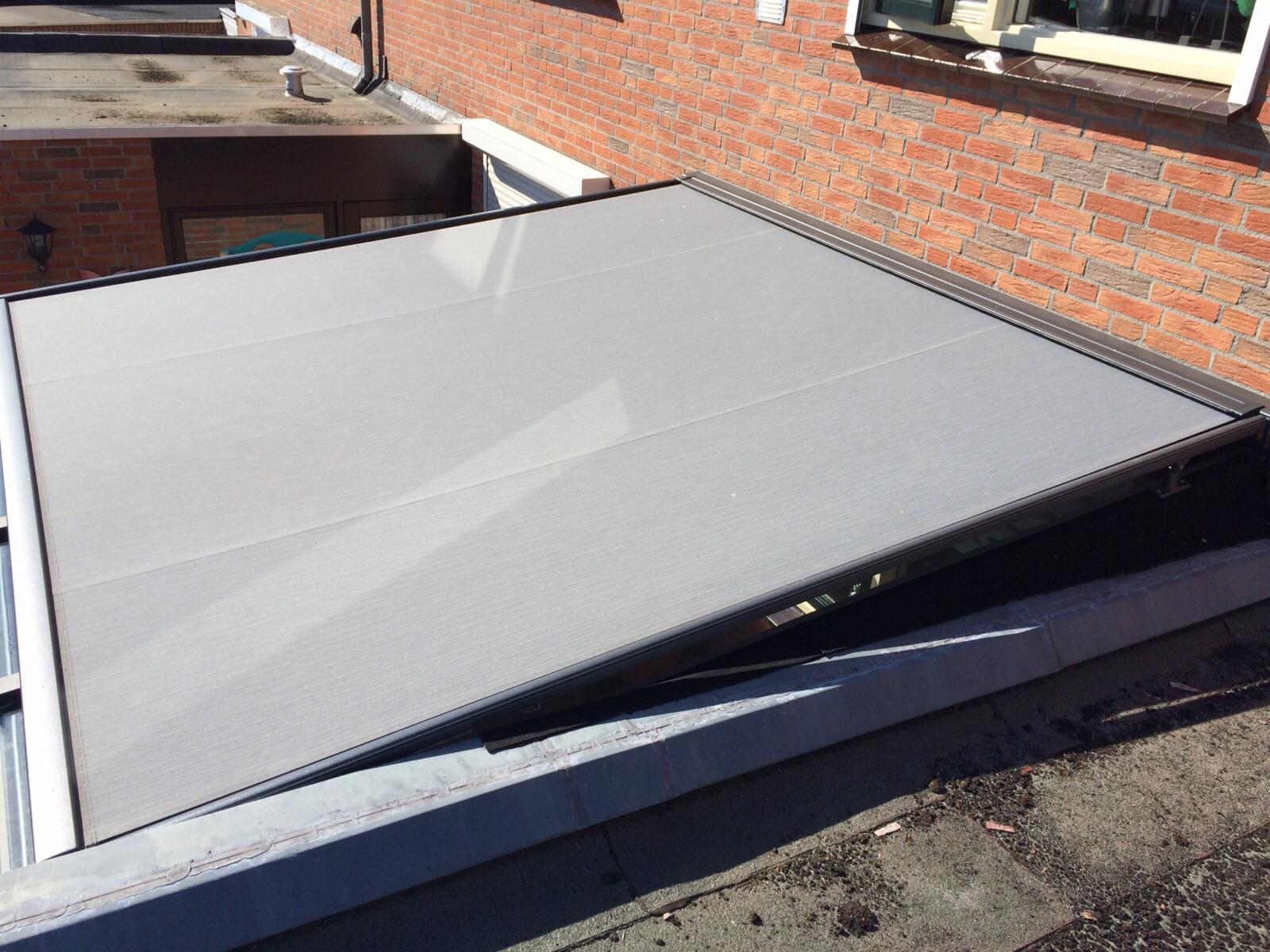 Grijze zonwering over glazen dak van serre