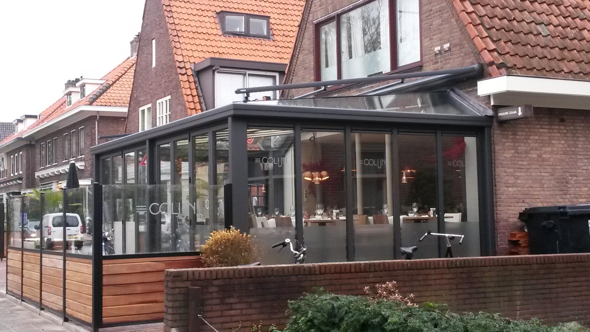 Serre met vouwwand aan restaurant met terras aan voorzijde.