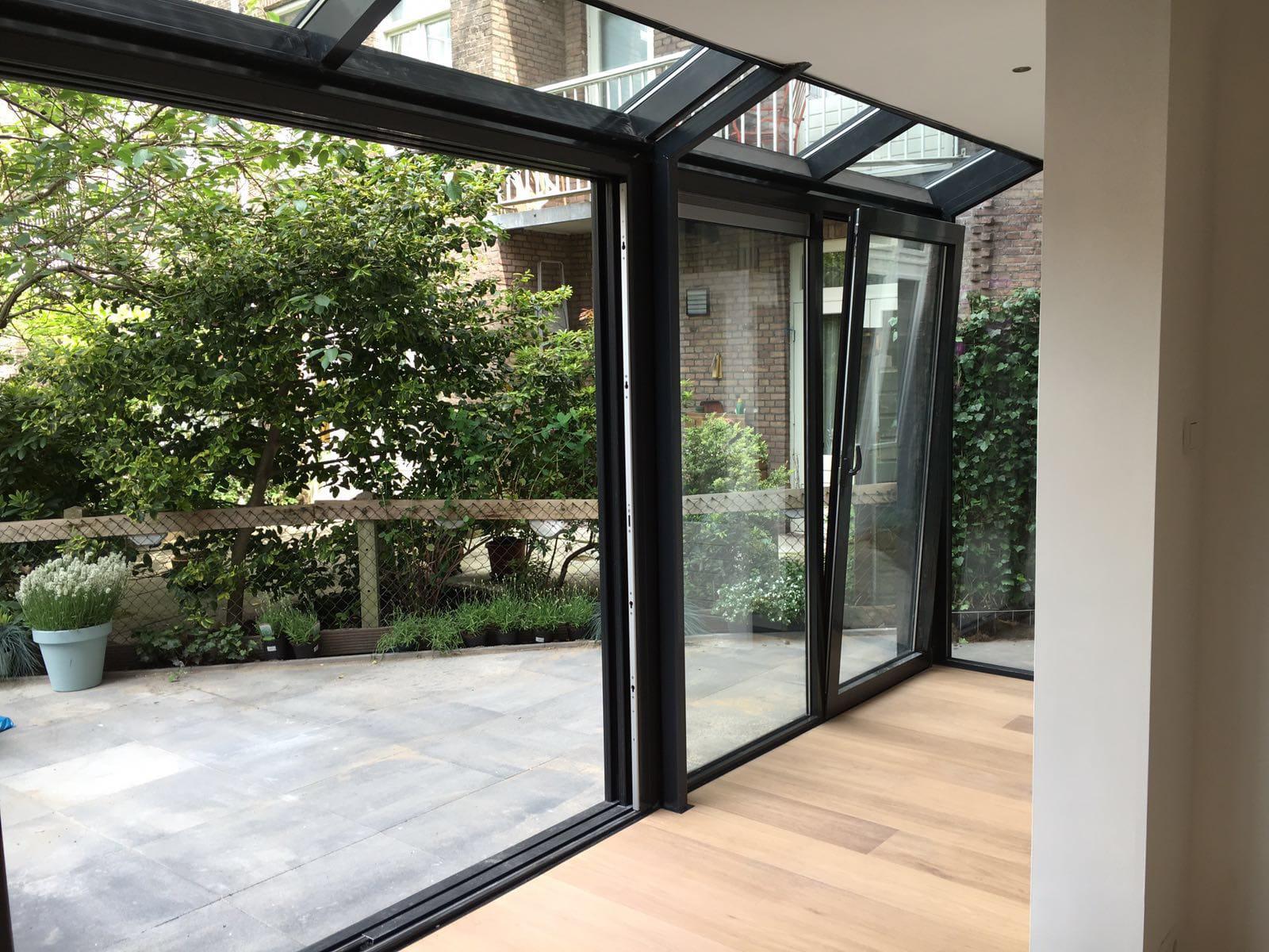 Binnenzijde zwarte serre tegen plat dak knik met schuifpui en draaikiep deur