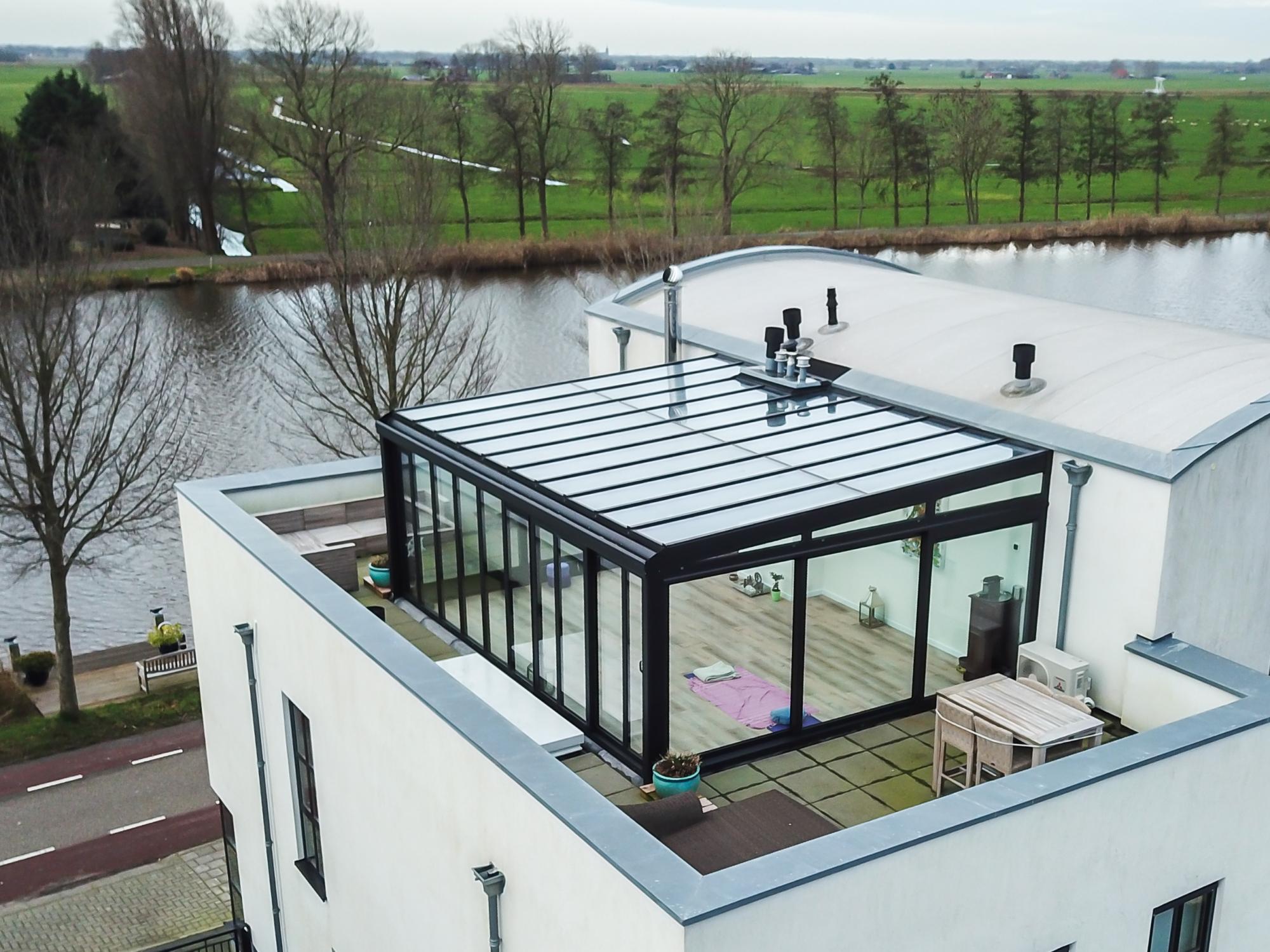 Zwarte serre met lessenaars dak boven op dakterras woning