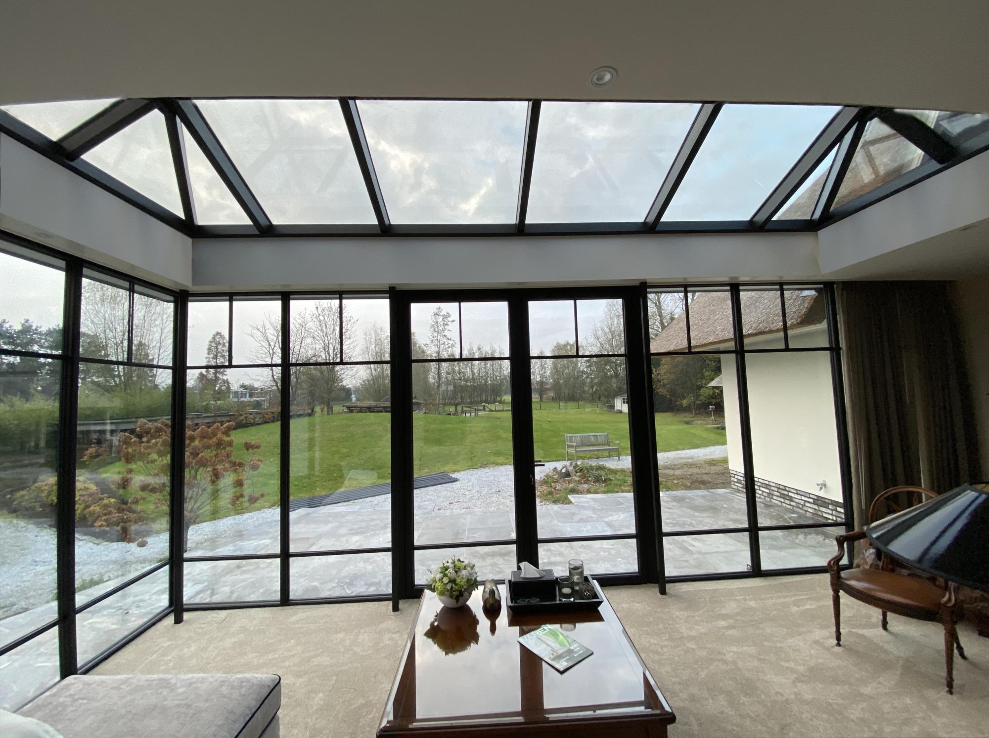 Steellook serre met schuifdeur vanuit binnen met uitzicht op grote tuin.