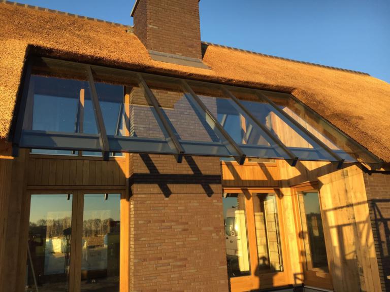 Glazen terrasoverkapping in huis met rieten dak
