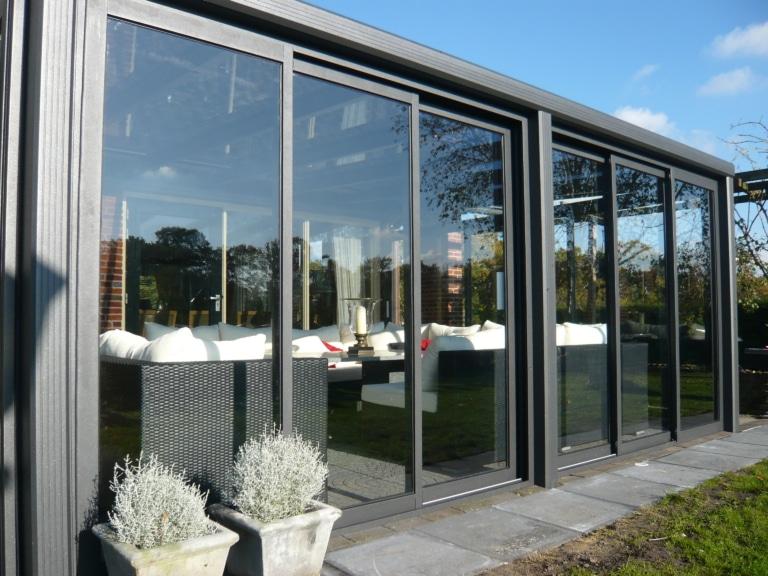 Grijze tuinkamer met schuifwand met glazen lessenaars dak.