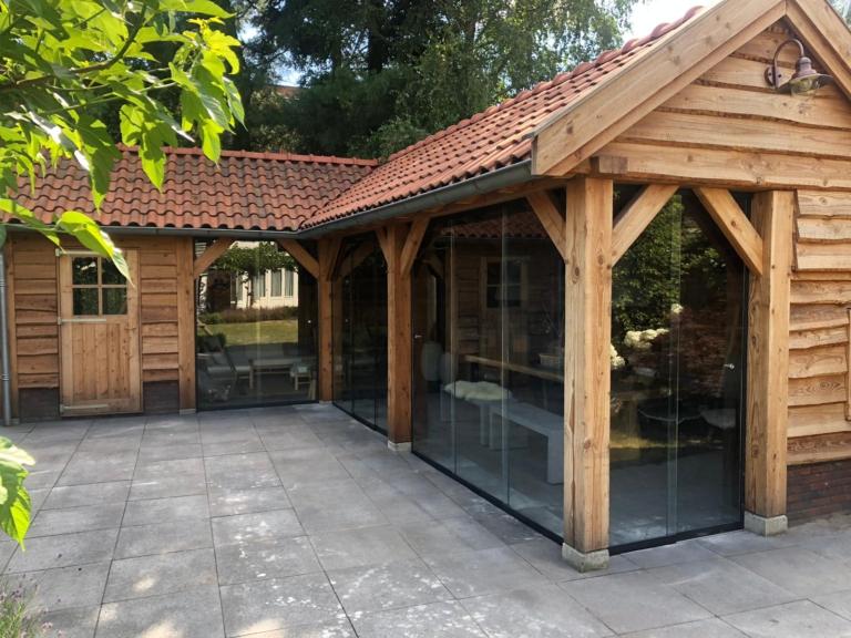 Glazen schuifwand in houten tuinkamer met puntdak