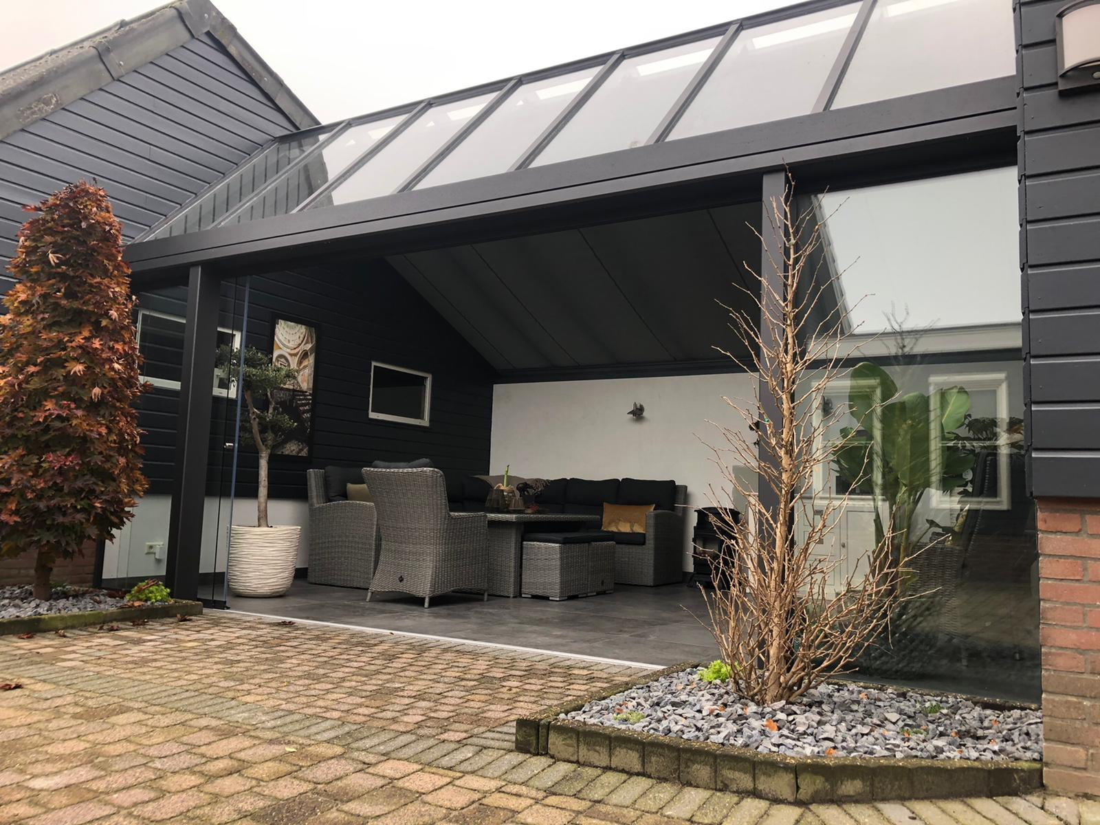 Grijze aluminium tuinkamer met zadeldak en schuifwand tussen twee muren.