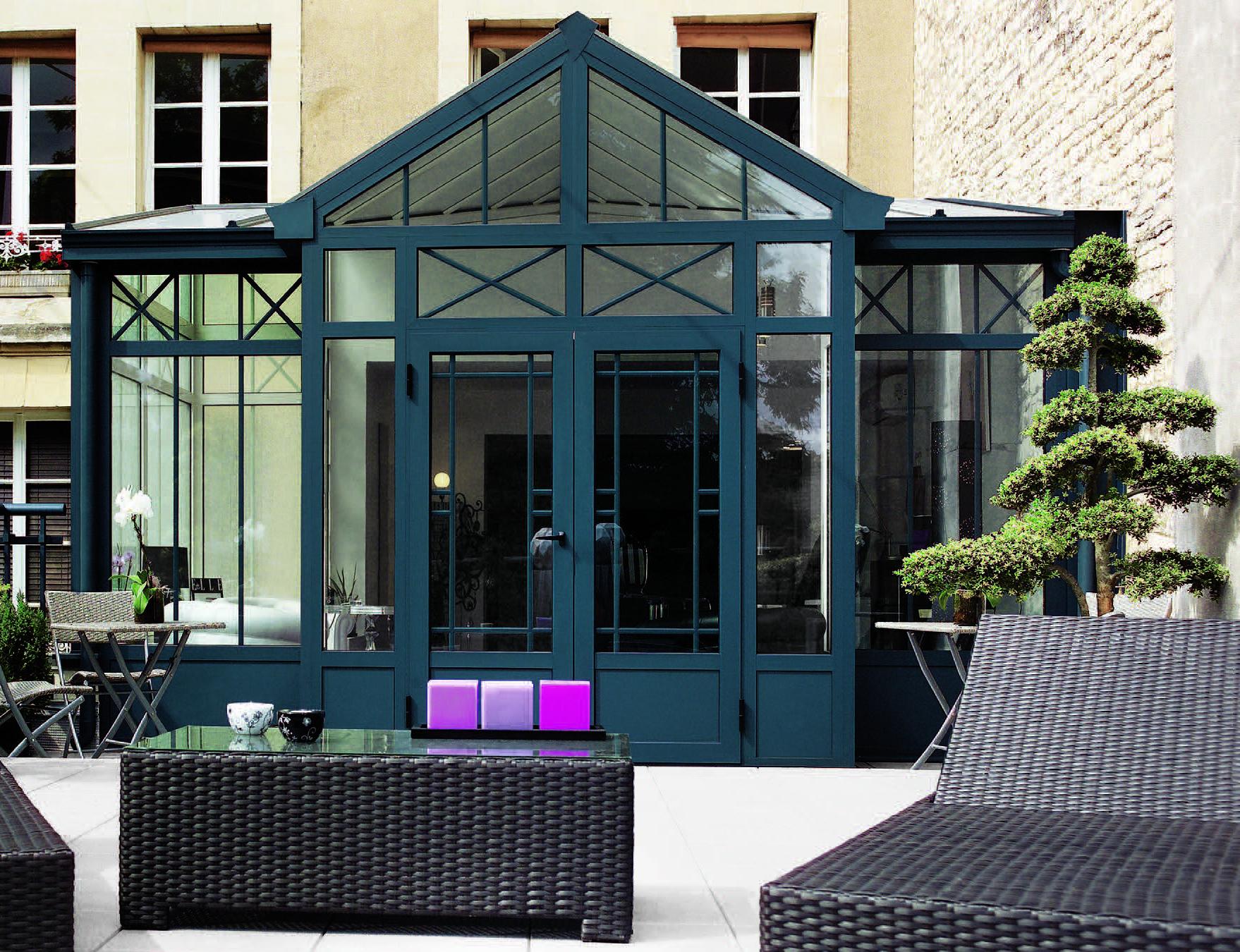Groene victoriaanse serre met klassiek ontwerp en openslaande deuren