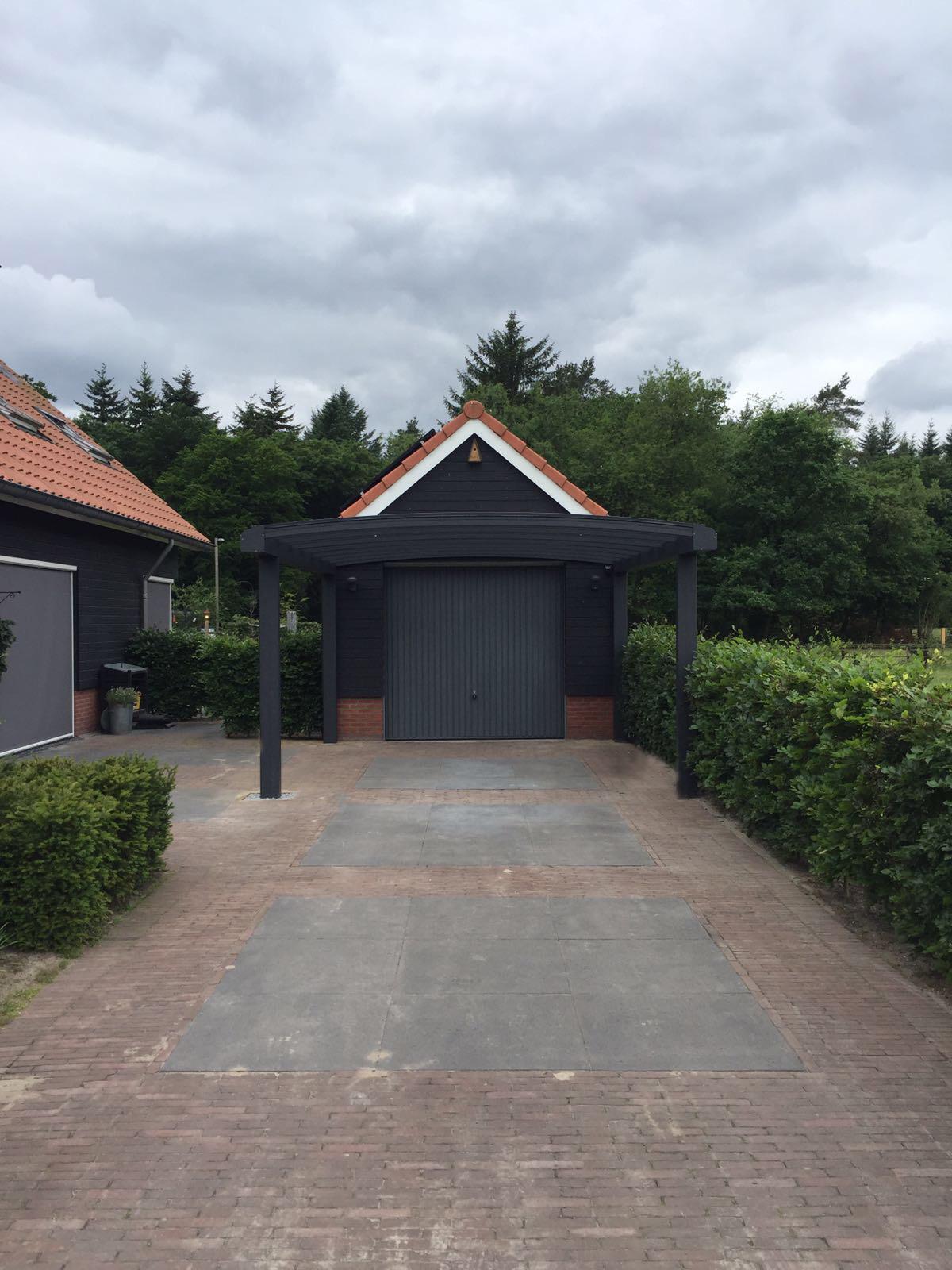 Vooraanzicht van grijze gebogen carport tegen zwarte houten garage