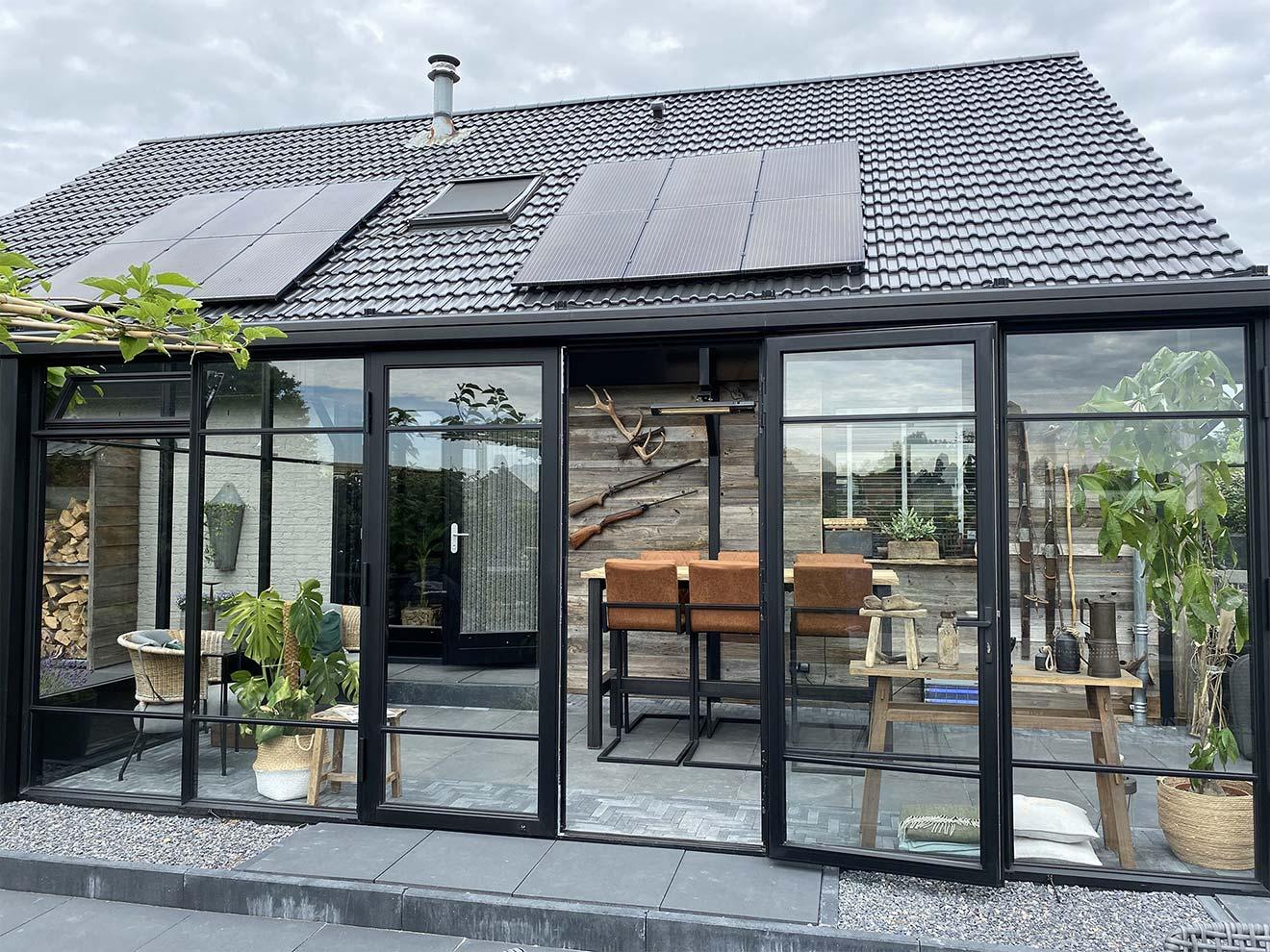 Zwarte serre aanbouw met plat dak en openslaande stolpdeuren