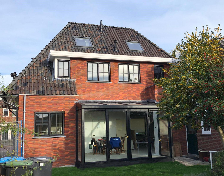 Zwarte zwarte steellook serre met lessenaarsdak op veranda aan stenen huis.